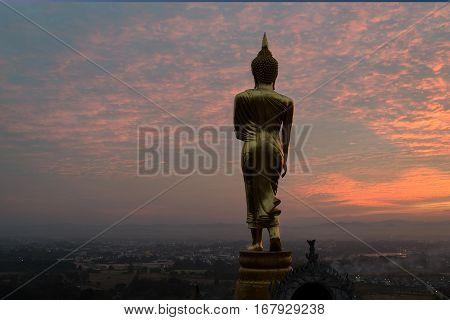 Sunrise at golden buddha statue in Khao Noi temple Nan Province Thailand.