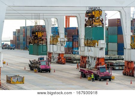 Container cargo freight ship with working crane loading bridge in shipyard for Logistic Import Export background.