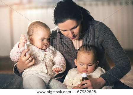 Mother giving medicine to twins babies at home