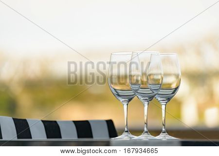 Three empty wine glasses arranged on a table in an open air restaurant or bar.