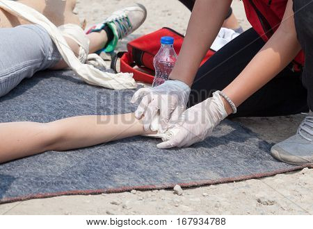 Paramedic bandaging the hand of an injured person