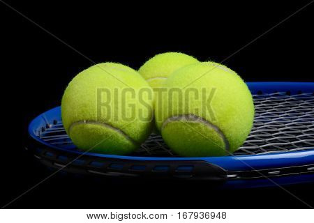 tennis balls and tennis racket black background