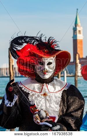 VENICE, ITALY - MARCH 04, 2011: Participant in colorful costume and mask of cat in front of San Giorgio Maggiore church during traditional famous Carnival taking place each year on February in Venice.