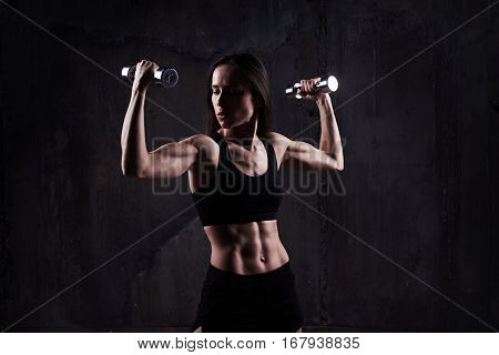 Close-up of active sportive athletic woman looking at bicep while pumping up dumbbells. Biceps concept. Fitness sport training lifestyle. Fitness woman with dumbbells working out