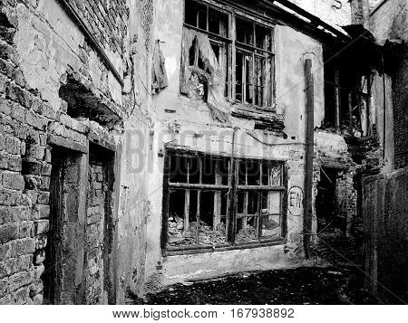 Destroyed house in dark colors as a symbol of devastation, desolation, destruction and loss, or war. Monochrome variant. Horizontal.