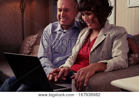 Side mid shot of man in blue shirt and woman in blazer, smiling and watching something funny on laptop. Sitting on the brown sofa with patterned cushions