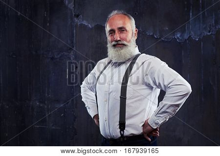 Close-up of confident man wearing black shirt and suspenders. Looking at the camera, isolated over black background. Shrewd look of mature man