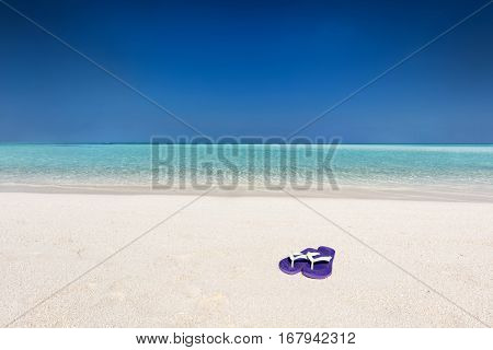 Flip-flops on sand on tropical beach, clear turquoise ocean in Maldives. Vacation, travel