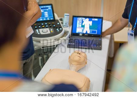 Team of medical doctor students learning to do advanced medical examination of patient with ultra sound scanner machine on ultrasound techniques workshop.