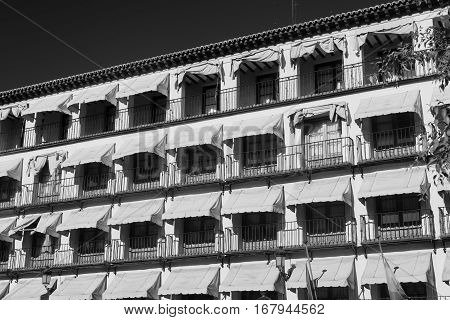 Toledo (Castilla-La Mancha Spain): facade of historic building with balconies and yellow curtains in the Zocodover square. Black and white