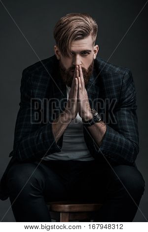 Perfect man. Beautiful young man keeping hands clasped and looking at camera while sitting against grey background