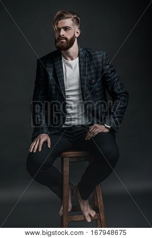 Confident in his style. Full length of handsome young man looking away while sitting on chair against grey background