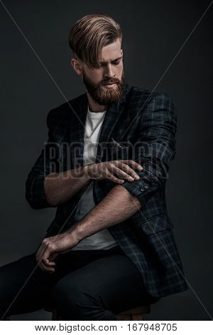 Used to look perfect. Stylishly dressed young man adjusting his jacket while sitting against grey background