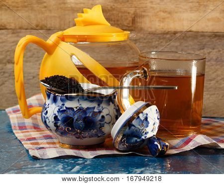 Food background. Teapot glass and tea leaves.