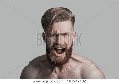 Feeling angry. Portrait of furious young man looking at camera and shouting while being in front of grey background