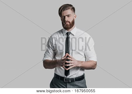 Ready to negotiate. Thoughtful young businessman holding hands clasped and looking at camera while standing against grey background