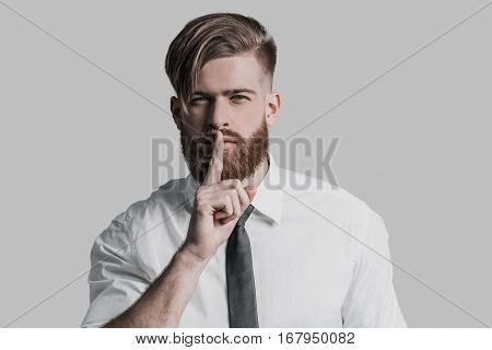 Keep my secret. Young businessman holding finger on lips and looking at camera while standing against grey background