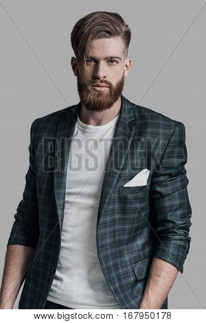 Amazing look! Attractive man with long hair and beard looking at camera while standing against grey background