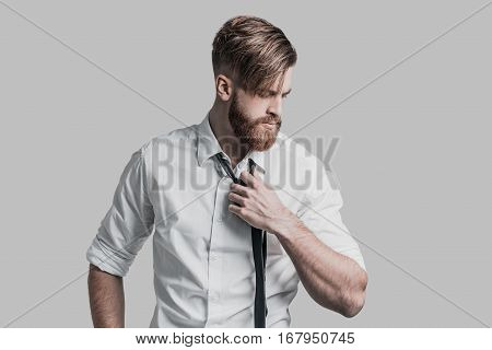 Time to rest. Young businessman taking off necktie and looking away while standing against grey background