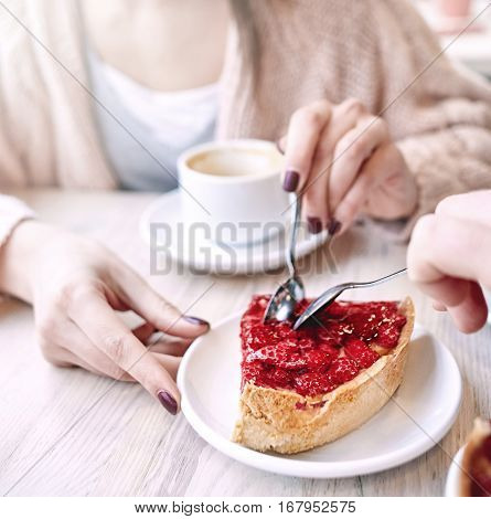 couple eating a dessert by spoon in a cafe on a date. woman holds a saucer with a cake and smiling. Love story and Valentines Day concept. focus on a pie.