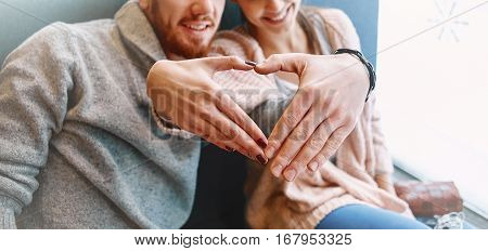 man and woman smiling with hands depict the heart. Two people, man and woman in cafe communicate, laughing and enjoying the time spending with each other. Couple in love on a date. Love story and Valentines Day concept