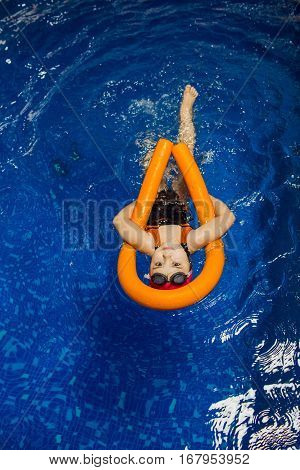 child girl swimming on her back with a pool noodle in swimming pool, top view floating.