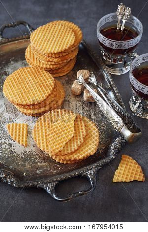 French waffles traditional norman biscuit on vintage tray and two cup tea dark photo