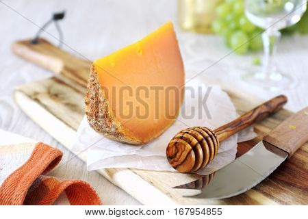 Mimolette cheese green grapes bottle of white wine and wineglass