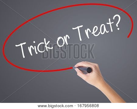 Woman Hand Writing Trick Or Treat? With Black Marker On Visual Screen.