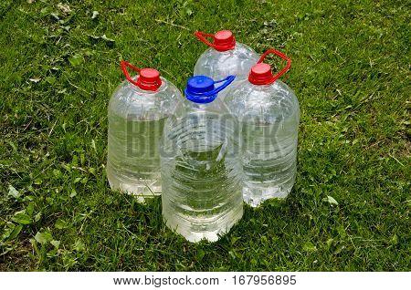 four plastic water bottle on garden grass