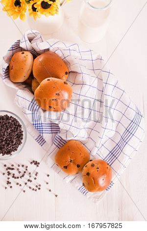 Chocolate chip brioche with bottle milk on checked napkin.