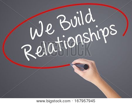 Woman Hand Writing We Build Relationships With Black Marker On Visual Screen