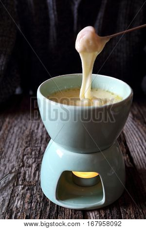 Traditional cheese fondue on wooden table. Focus selective