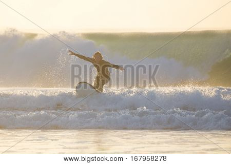 EL Cotillo, Spain - Dec 22, 2015: Surfer beginner learnig to surf at El Cotillo beach, famous surfing destination on Fuerteventura, Canary Islands, Spain on December 22, 2015.