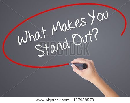 Woman Hand Writing What Makes You Stand Out? With Black Marker On Visual Screen
