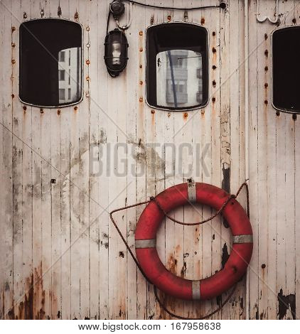 Lifebuoy between two windows on a wooden wall