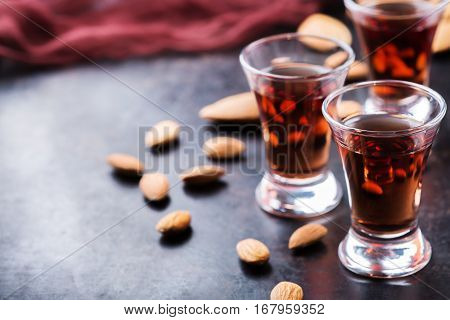 Food and drink, party, alcohol concept. Traditional italian sweet almond liquor amaretto on a grunge black table, digestif beverage, copy space background