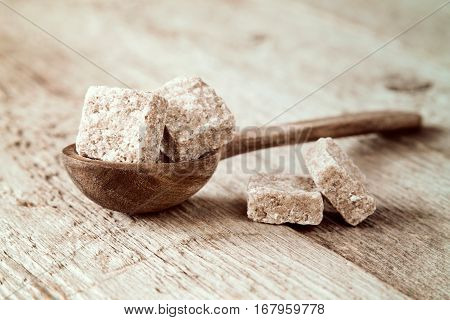 Small wooden spoon and brown cane sugar