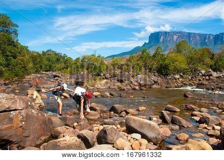 Tourists crossing Kukenan River, Kukenan Tepui on the Horizon, Gran Sabana, Venezuela