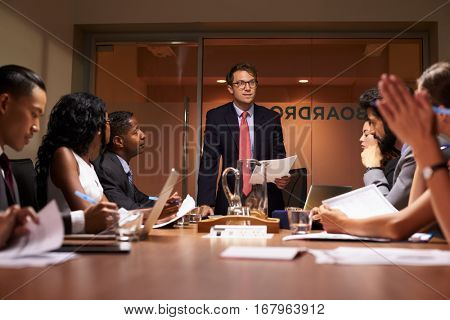 Businessman stands addressing team at meeting, low angle