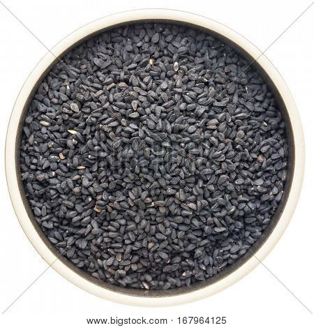 black cumin seeds (Nigella sativa) in a round ceramic bowl isolated on white