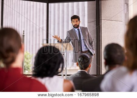 Hispanic man presenting business seminar leaning on lectern