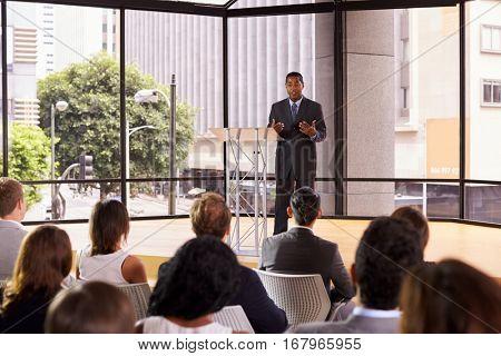 Black businessman presenting seminar gesturing to audience