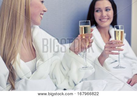 holidays, celebration, people and drinks concept - two happy women in bathrobes with champagne glasses at hotel