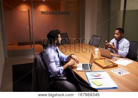 Two middle aged businessman working late in an office