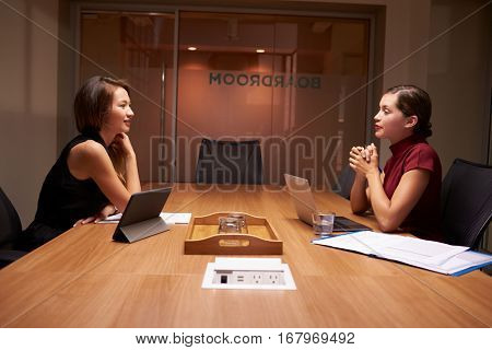 Two businesswomen working late sitting opposite each other