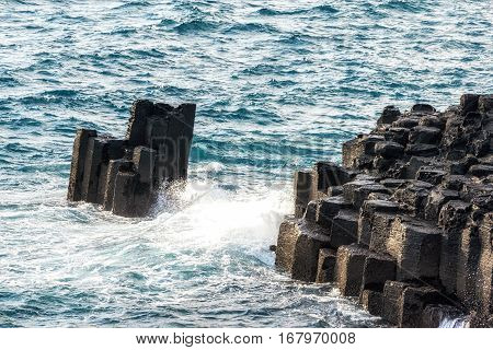 waves hitting the side of daepo jusangjeolli cliff stone pillars in jejudo south korea