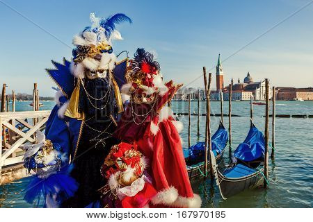 VENICE, ITALY - MARCH 04, 2011: Two participant in red and blue costumes and masks as San Giorgio Maggiore on background during traditional Carnival taking place each year on February in Venice.