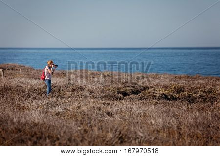 Young lady with backpack taking a picture