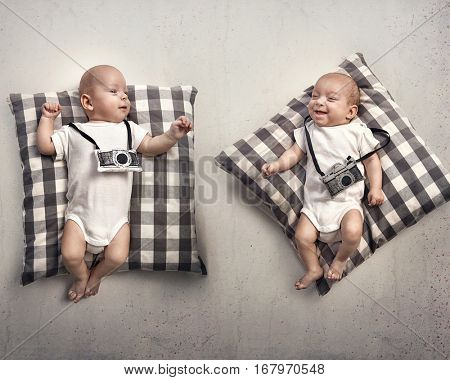 Two little twin infants lying and playing